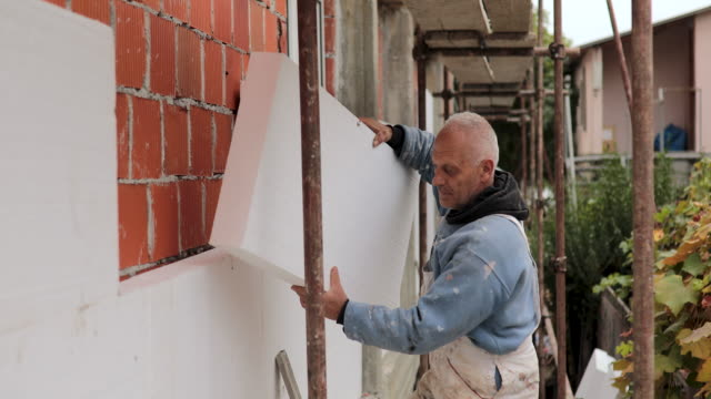 Man installing styrofoam insulation board for energy saving on exterior wall of house Man installing styrofoam insulation board for energy saving on exterior wall of house positioning stock videos & royalty-free footage