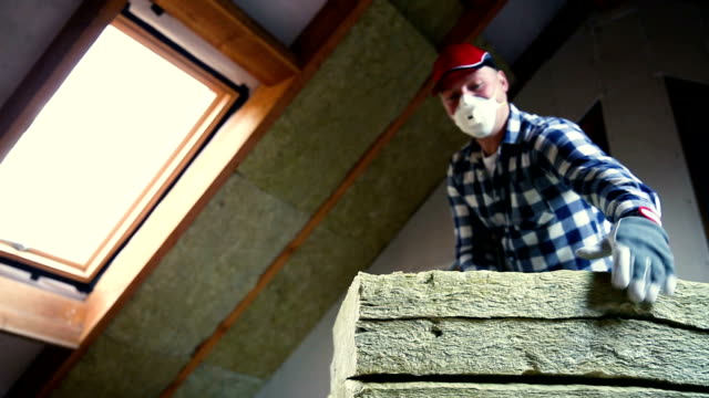 vídeos de stock e filmes b-roll de man installing thermal roof insulation layer - using mineral wool panels. attic renovation and insulation concept - isolador