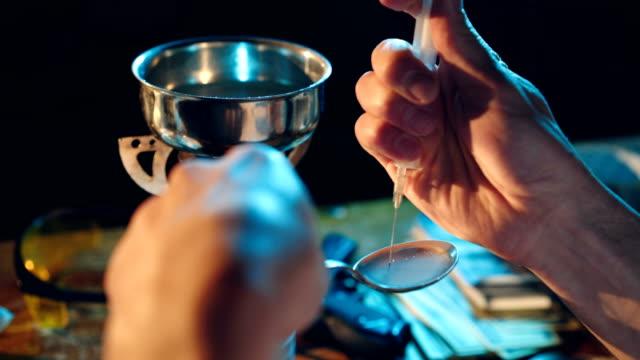 stockvideo's en b-roll-footage met man maakt een drugsverslaafde zitten aan de tafel drugs. - amfetamine