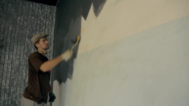 Man is actively using a fur roller when painting walls gray paint video