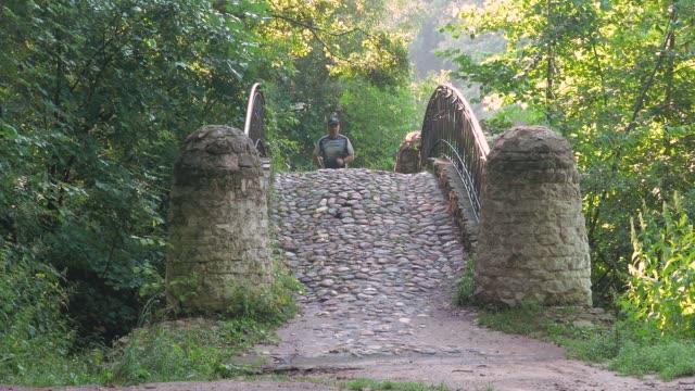 en man är en idrottsman, leder en hälsosam livsstil. han kör över bron, i parken på en sommardag. - tävlingsdistans bildbanksvideor och videomaterial från bakom kulisserna