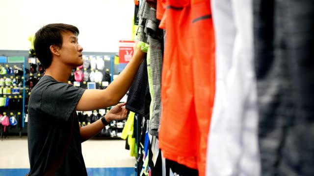 man is choosing clothes at sport department - sprzęt sportowy filmów i materiałów b-roll