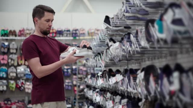 man is choosing sneakers in hall of shop of footwear - video