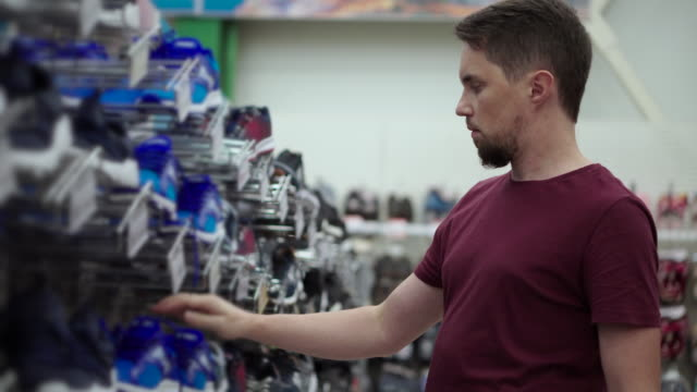 man is choosing sportive shoes in footwear store - vídeo