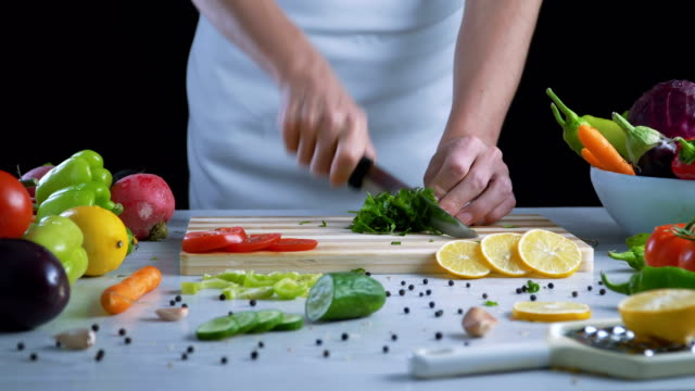 Man is chopping parsley in the kitchen Man is chopping parsley in the kitchen parsley stock videos & royalty-free footage