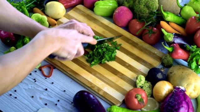 Man is chopping parsley on cutting board Man is chopping parsley on cutting board parsley stock videos & royalty-free footage
