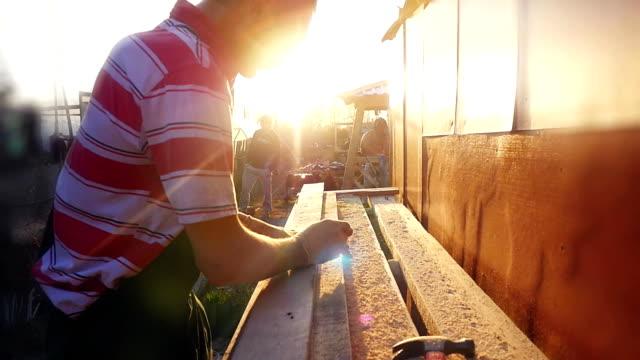 L'homme est l'artisanat travaillant à un banc de travail avec des outils électriques en slowmotion pendant le coucher du soleil avec la belle lumière parasite. 1920 x 1080 - Vidéo