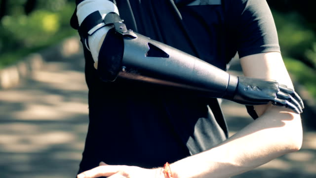 A man is crossing his artificial arm with a healthy one. Human cyborg concept. A man is crossing his artificial arm with a healthy one. 4K prosthetic equipment stock videos & royalty-free footage