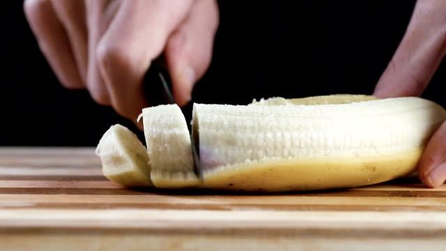vídeos de stock, filmes e b-roll de homem é banana de corte na placa de corte em câmera lenta - fruit salad