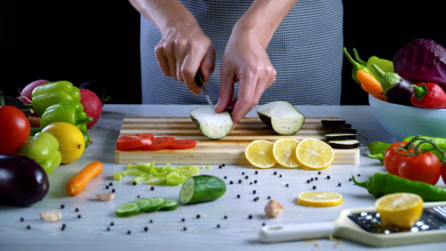 man is cutting eggplant on cutting board in the kitchen - melanzane video stock e b–roll