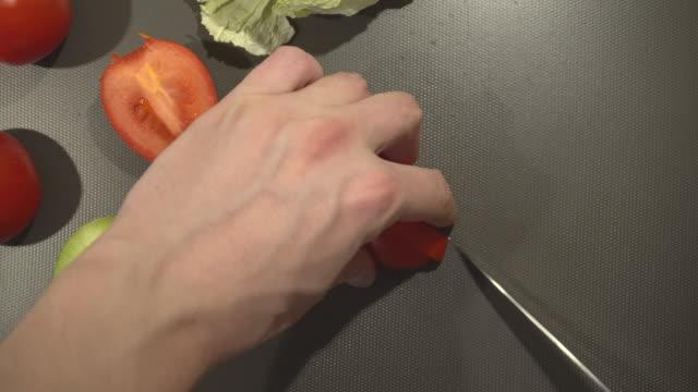 Man is cutting fresh organic tomato for vegan dishes Man is cutting fresh organic tomato for vegan dishes tomato salad stock videos & royalty-free footage