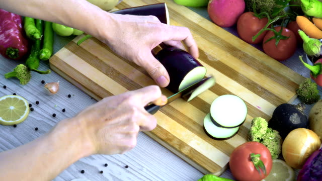 man is cutting vegetables in the kitchen, slicing eggplant - melanzane video stock e b–roll