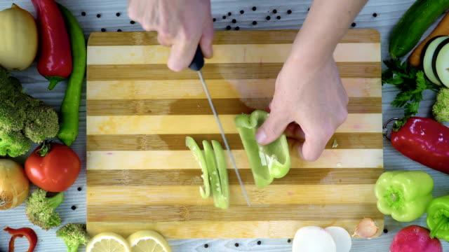 vídeos y material grabado en eventos de stock de el hombre es vegetales de corte en la cocina, cortar el pimiento verde - pimiento verde