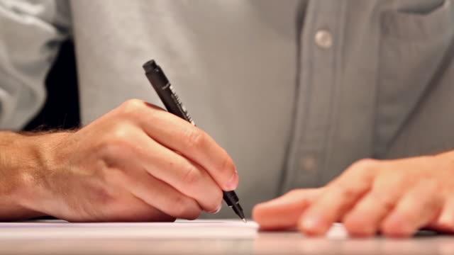 vidéos et rushes de l'homme dessine ou écrit sur une feuille de papier blanche. macro shot d'affaires portant une chemise et l'écriture sur le papier derrière le bureau - notaire