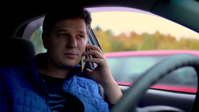 A man is drinking coffee and talking on his mobile phone while driving a car. video
