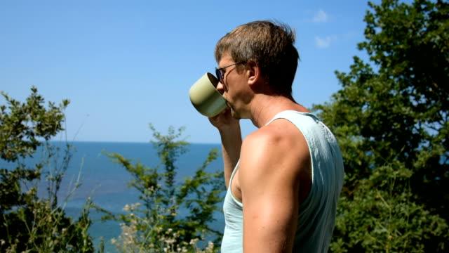 vidéos et rushes de un homme boit du café. mer et vacances. - man drinking terrace