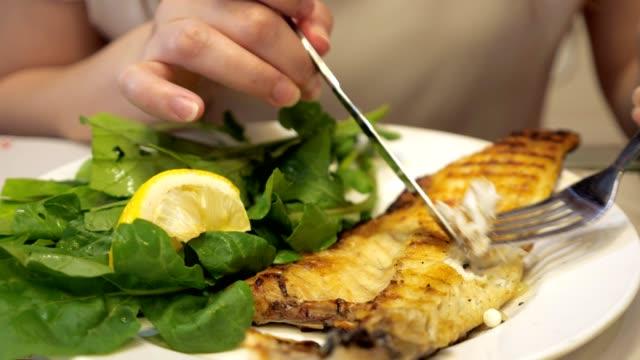 der mensch isst bratfisch mit gabel und messer im restaurant, gericht nahaufnahme. - fische und meeresfrüchte stock-videos und b-roll-filmmaterial