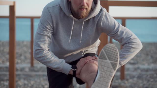 man is exercising outdoors, stretching leg in summer morning - rozciągać filmów i materiałów b-roll