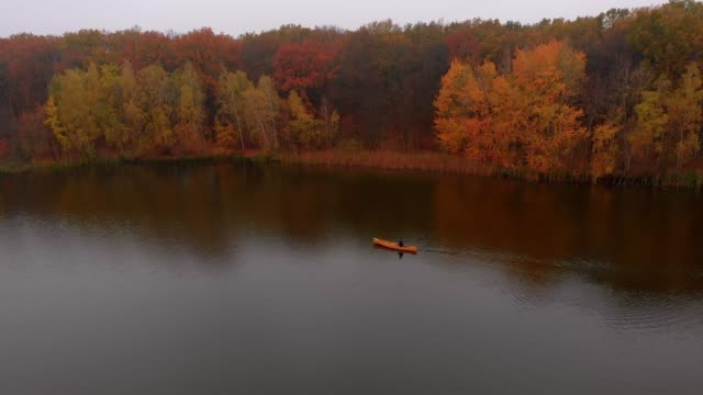 vídeos de stock e filmes b-roll de man is floating in yellow boat canoe on the river near colorful trees at golden autumn - fishman