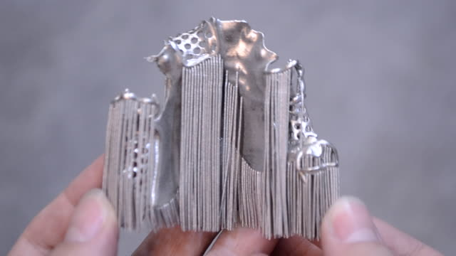 Man is holding object printed on metal 3d printer.