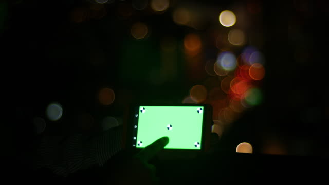 Man is holding smartphone with green screen at evening time
