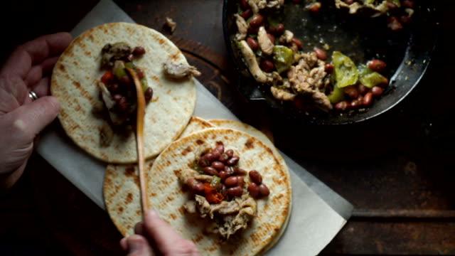 vídeos de stock e filmes b-roll de man is laying a ready-made chicken with pepper on the tortilla. video - produto de carne
