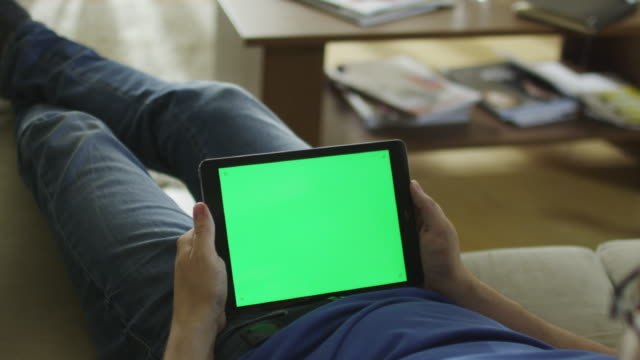 Man is Laying on Couch at Home and Watch on Tablet with Green Screen in Landscape Mode video