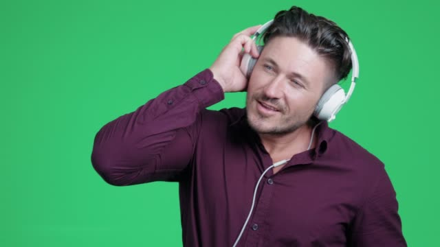 Man is listening music and dancing at green screen background