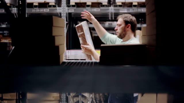 Un homme cherche le paquet nécessaire, en prenant l'une de l'étagère avec les cartons dans un entrepôt de stockage - Vidéo
