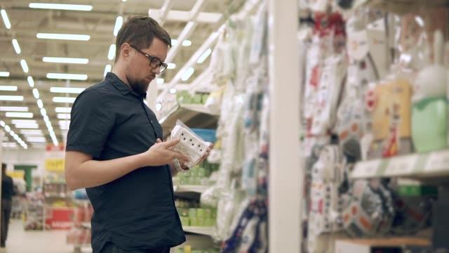 vidéos et rushes de l'homme est la recherche de socket dans un département électrique de magasin de matériaux de construction - vidéos de rallonge électrique