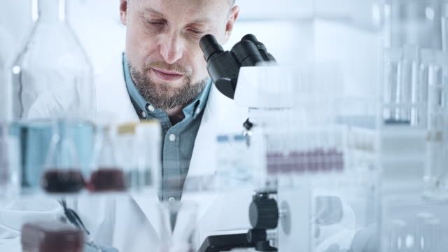 Man is looking through a microscope A close-up of the eyes and face of a man looking through a microscope in a laboratory biochemistry stock videos & royalty-free footage