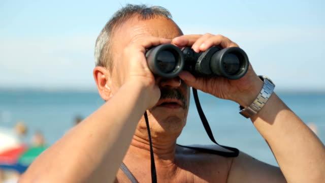 Man is looking through binoculars on beach video
