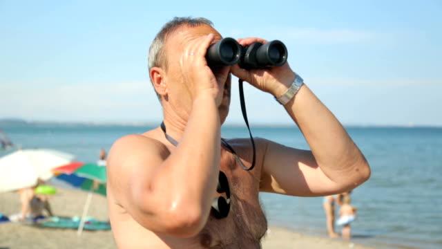 mann sucht fernglas am strand - sonnenschirm stock-videos und b-roll-filmmaterial