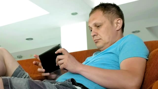 A man is on his mid pad tablet on a couch A man is shown enjoying on a couch working on his mid pad. Tablets made a remarkable change in the tech industry. Extremely portable and has a good battery life. short length stock videos & royalty-free footage