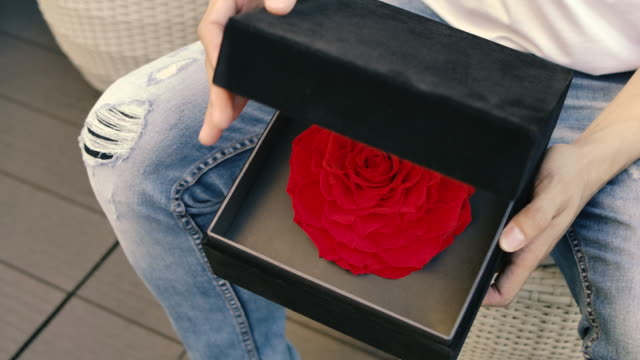 A man is opening a black box of roses valentine's surprise gift for his girlfriend