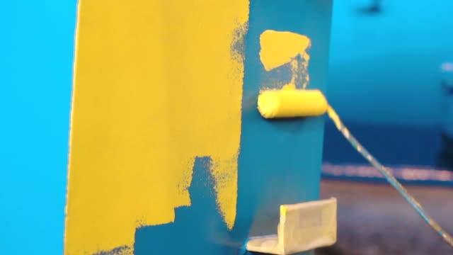 man målar stora blå metall detalj av hand rulle till gul färg - blue yellow bildbanksvideor och videomaterial från bakom kulisserna