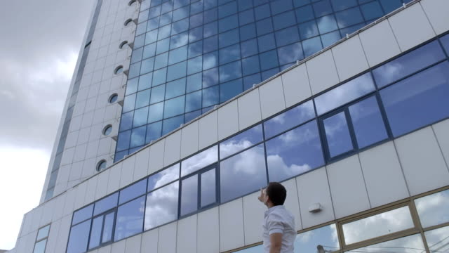 Man is pointing at modern office building against cloudy sky video