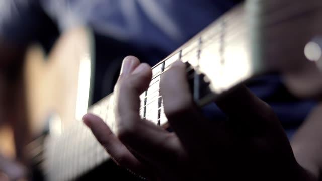 vídeos de stock, filmes e b-roll de um homem está praticando tocando uma nota em uma guitarra. - música acústica