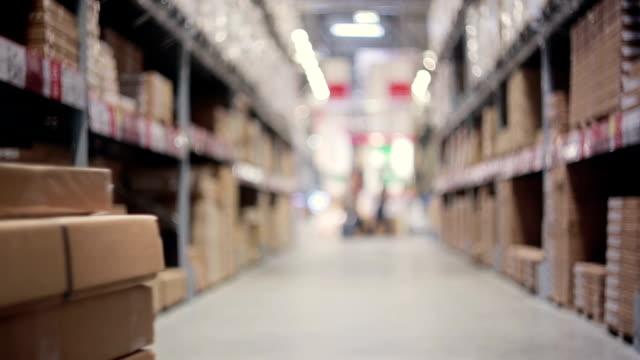 Un homme pousse un chariot plein de boîtes à ce sujet entre les palettes avec des boîtes en carton dans un entrepôt de stockage - Vidéo