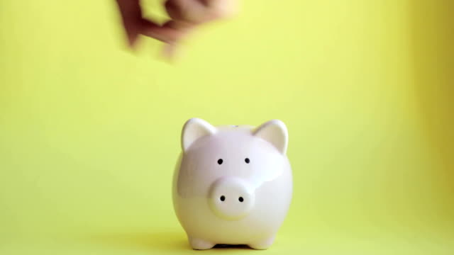 Man is putting coins in pink piggy bank on yellow backgroung, hand closeup