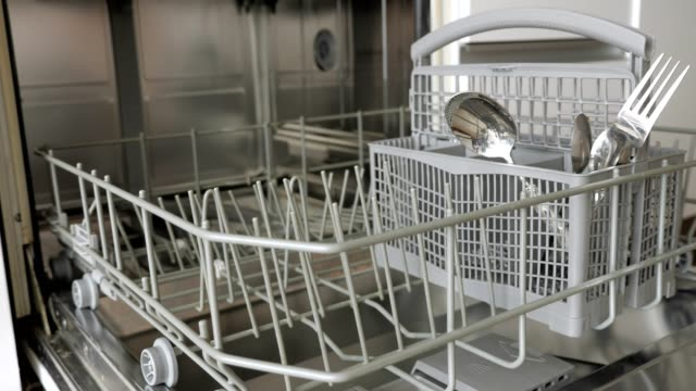 Man is putting dirty tableware in dishwasher, hands closeup. Man puts a dirty plates and cutlery in dishwasher and pushes the basket with kitchenware. Top view, close-up hand. dishwasher stock videos & royalty-free footage
