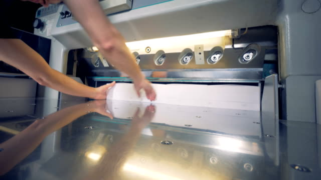 A man is putting four stacks of paper under a cutter which shears its sides