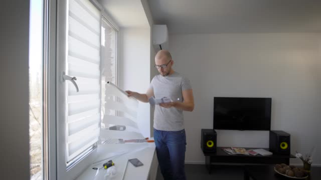 vídeos de stock e filmes b-roll de man is reading an installation instruction for curtains on windows and looking on details, standing in living room of his house - pendurar
