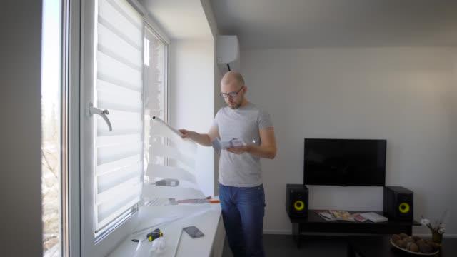man läser en installationsanvisning för gardiner på windows och titta på detaljer, stående i vardagsrummet i sitt hus - hänga bildbanksvideor och videomaterial från bakom kulisserna