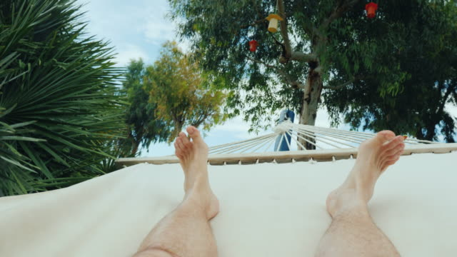 A man is resting in a hammock, a first-person view. In the frame only the legs are visible A man is resting in a hammock, a first-person view. In the frame only the legs are visible. 4K video physical position stock videos & royalty-free footage