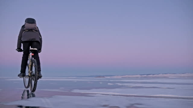 Man is riding a bicycle on ice. The cyclist is dressed in a gray down jacket, backpack and helmet. Ice of the frozen Lake Baikal. The tires on the bicycle are covered with special spikes.