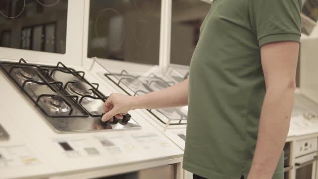 l'uomo ruota le maniglie del pannello di cottura della mostra in un negozio, da vicino - elettrodomestico attrezzatura domestica video stock e b–roll