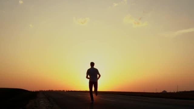 en man kör mot solnedgången. - jogging hill bildbanksvideor och videomaterial från bakom kulisserna