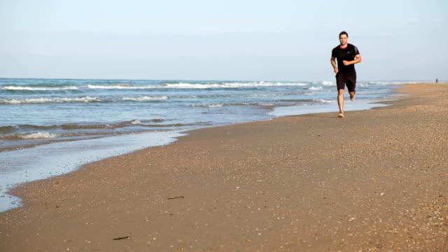 Man is running along the beach video
