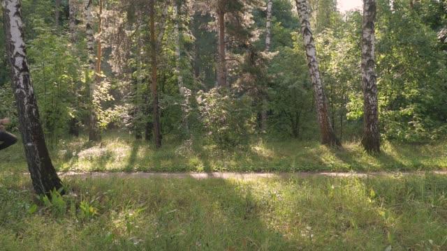 en man kör i parken på en sommardag. han tränar och utför övningar för utvecklingen av löpning. - tävlingsdistans bildbanksvideor och videomaterial från bakom kulisserna